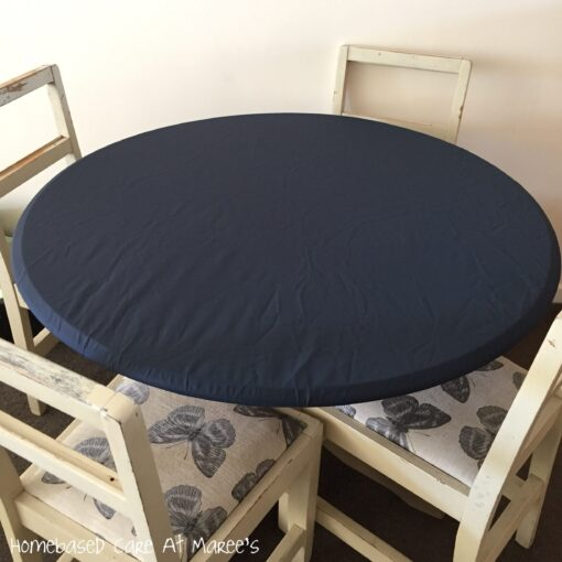 Navy blue round elasticated fitted tablecloth on a table