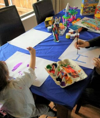 Kids painting at a dining room table protected with a Mud Mates elasticated fitted tablecloth