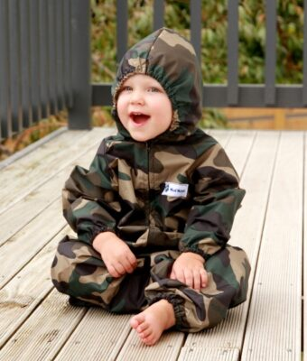 Young child sitting wearing Mud Mates NZ-made green camo waterproof coveralls