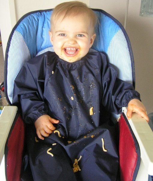 Baby in highchair messy with food wearing a Mud Mates NZ-made long sleeve bib