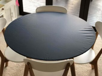 Black round elasticated fitted tablecloth on a table