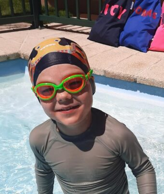 Young boy in swimming pool wearing Otto the Octopus lycra kids swim cap and Funkies orange/green kids goggles