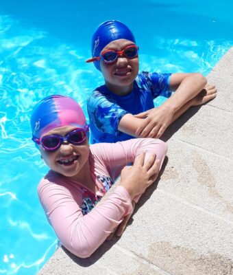 A girl and boy at edge of swimming pool wearing silicone kids swim caps and Funkies kids goggles