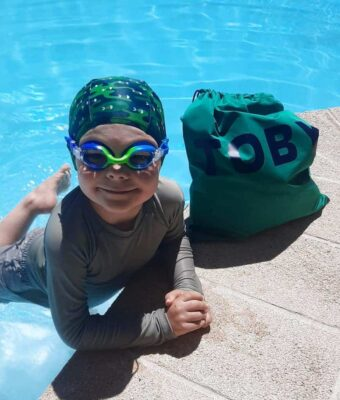 Young boy at swimming pool edge with a personalised NZ-made swim bag, blue/green kids goggles and green camo fish swim cap