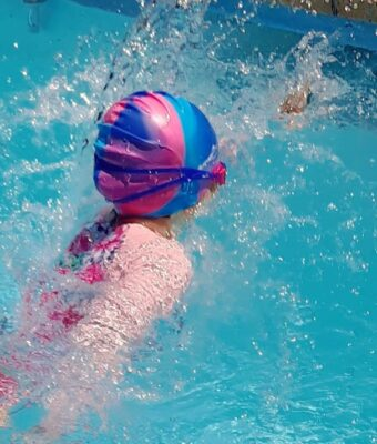 Girl swimming in pool wearing a pink/blue multi-coloured silicone swim cap
