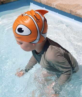Young boy in swimming pool wearing an orange fish silicone kids swim cap