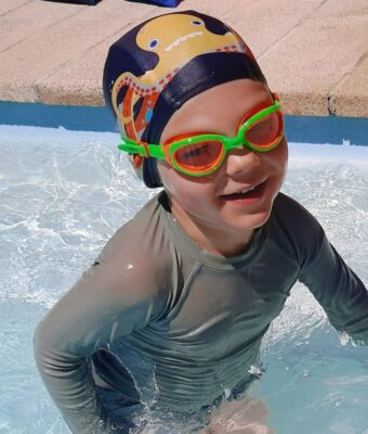 Young happy boy in swimming pool wearing Otto the Octopus lycra kids swim cap and orange/green Funkies kids goggles