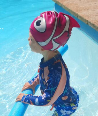 Toddler girl in swimming pool wearing a silicone pink fish swim cap