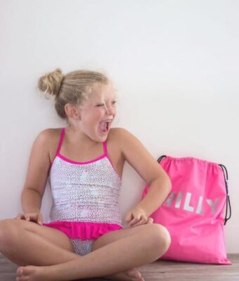 Girl in her togs sitting by her Mud Mates pink personalised swim bag / wet bag