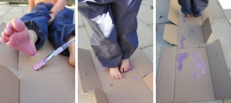 Toddler and young child with paint on their feet walking on carboard: sensory feet play