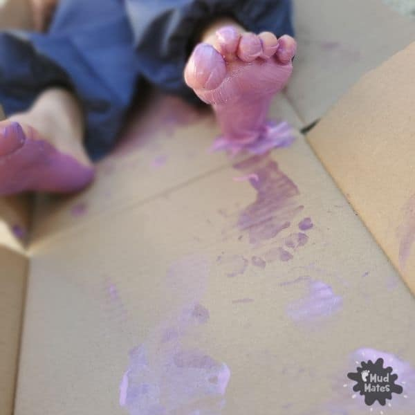 Sensory Feet Play Ideas - toddler with paint on her feet and footprints on cardboard